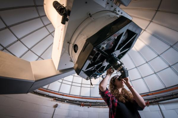 Astronomy student looks through telescope in the observatory.